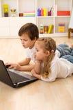 繁忙的集中的孩子膝上型计算机工作 免版税库存图片