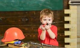 繁忙的面孔的小孩在家使用与螺丝刀工具在车间 孩子作为杂物工的男孩戏剧 童年概念 孩子 免版税库存图片