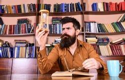 繁忙的面孔阅读书的,在背景的书架人 教训和时间概念 有镜片的科学家坐在 库存照片