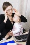 繁忙的婴孩她的母亲 免版税图库摄影