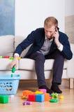 繁忙的年轻爸爸清洗玩具 免版税库存图片