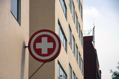 红十字会急救/垂悬大厦的边的医疗标志[标志] 库存照片