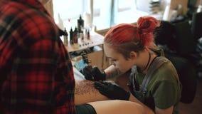 红发在女孩客户lef的女孩纹身花刺艺术家刺字的图片在演播室 股票录像