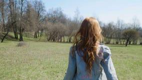 红发女孩充当一个晴朗的公园 股票录像