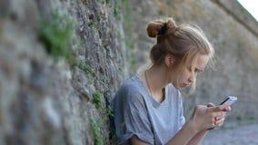 红发女孩写倾斜对一个石墙的一则消息 股票视频