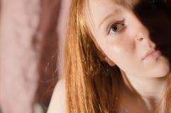 红发女孩半面孔 免版税库存照片