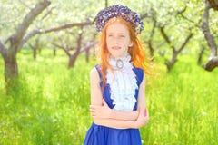 红发女孩在一个晴朗的庭院里 免版税图库摄影