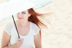 红发女孩在伞下坐海滩 库存照片