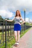 红发女孩在堤防站立 免版税库存照片