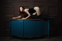 红发女孩在桌上的一条母狗 免版税图库摄影