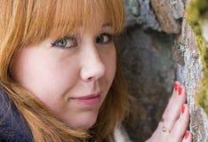 红发女孩接触石头 免版税库存图片