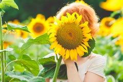 红发女孩用向日葵盖了她的面孔,在向日葵的领域的女孩隐姓埋名的享用的自然在日落的 免版税库存图片