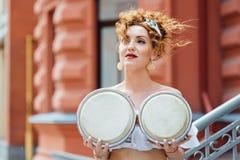 红发女孩用鼓盖她的胸口 免版税图库摄影