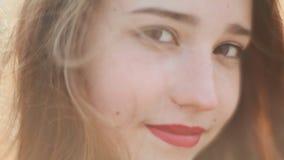 红发女孩的视域有微笑的在她的面孔 调直在风的头发 在他的胳膊的纹身花刺 特写镜头 股票视频