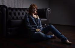 红发女孩的画象的牛仔裤衬衣和牛仔裤在黑沙发坐地板 免版税库存照片