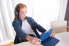 年轻红发女孩看在片剂的一部电影 免版税库存照片
