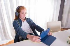 年轻红发女孩看在片剂的一部电影 免版税库存图片