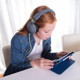 年轻红发女孩看在片剂的一部电影 库存图片