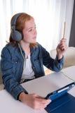 年轻红发女孩看在片剂的一部电影 库存照片