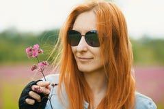 红发女孩骑自行车的人在他的手上拿着一朵花在手套 库存图片