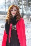 红发女孩画象一件红色雨衣的 库存图片