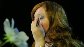 红发女演员在化装室在阶段做与准备蓝色的阴影的眼睛构成去 股票视频