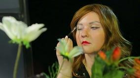 红发女演员在化装室在阶段做与准备黑的闪闪发光的眼睛构成去 影视素材
