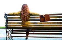 红发妇女坐与书的长凳 免版税库存图片