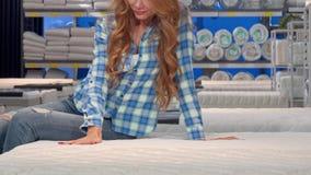 红发妇女微笑,坐一个新的矫形床垫在商店 股票视频