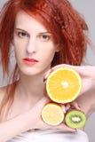 红发妇女用桔子、柠檬和猕猴桃 免版税库存照片