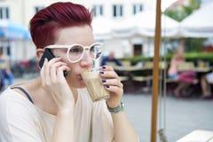 红发妇女饮用的咖啡和谈话在电话 免版税库存照片