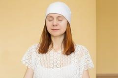 红发妇女画象一个帽子的与闭合的眼睛的瑜伽的我 图库摄影