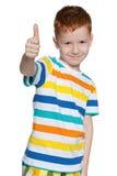 红发小男孩举行他的赞许 库存照片