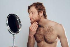 红发年轻人抚摸胡子,调查镜子 图库摄影
