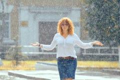 红发愉快的妇女在雨中 库存图片