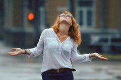红发愉快的妇女在雨中 免版税库存图片