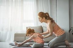 红发母亲和孩子训练在客厅 库存照片