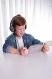 年轻红发男孩看在片剂的一部电影 免版税库存照片