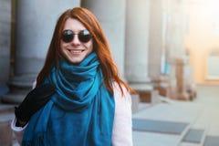 红发美丽的女孩在一条桃红色外套和蓝色围巾的都市背景中走,有太阳镜的 图库摄影