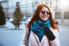 红发美丽的女孩在一条桃红色外套和蓝色围巾的都市背景中走,有太阳镜的 免版税图库摄影