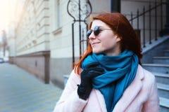 红发美丽的女孩在一条桃红色外套和蓝色围巾的都市背景中走,有太阳镜的 库存照片