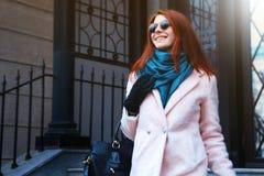 红发美丽的女孩在一条桃红色外套和蓝色围巾的都市背景中走,有太阳镜的 库存图片
