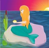 红发美人鱼在他的手上坐岩石并且拿着一朵花 水中女仙 免版税图库摄影