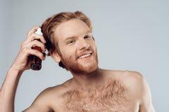 红发长毛的人洒在头发的香脂 图库摄影