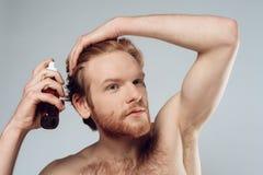 红发长毛的人洒在头发的香脂 免版税库存照片