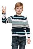 红发年轻男孩拿着胜利标志 免版税库存图片