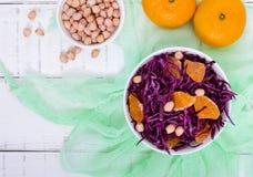 红叶卷心菜、蜜桔和未加工的花生饮食辣沙拉在一个陶瓷碗在白色木背景 免版税库存图片