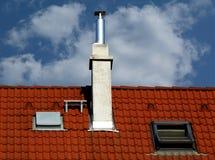红土屋顶和烟囱在天空蔚蓝下 免版税库存照片