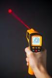 红外激光温度计在手中 免版税库存照片