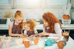 红头发人与黏土,瓦器孩子的母亲和两个女儿模子 库存照片